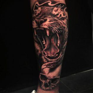 Tatuaje león y calavera en realismo realizado en el brazo.